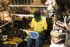 Un comerciante utilizando software Smart Work de IBM para su trabajo con un netbook en un mercado de artesanías de Johannesburgo, Sudáfrica.